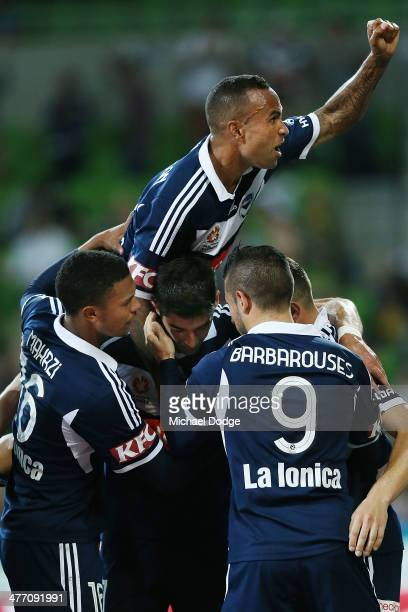 Archie Thompson of the Victory jumps on teamates as he celebrates a penalty goal by James Troisi during the round 22 ALeague match between Melbourne...