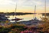 Sunset light over sailboats moored at small rocky island in the outer part of the archipelago. Old wooden sailboat in focus. Stockholm, Sweden.