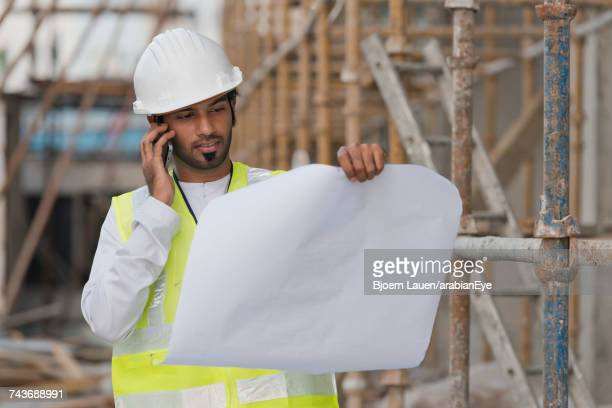 Architect analysing blueprint and talking on mobile.,Architect analysing blueprint and talking on mobile.