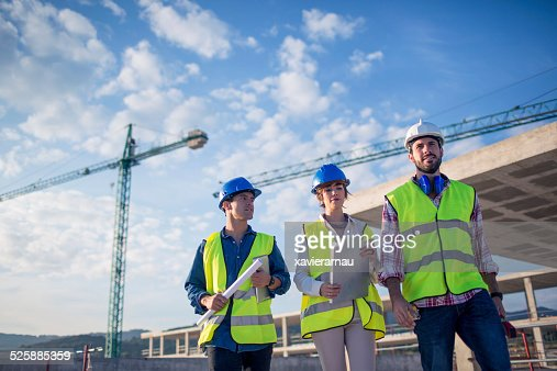 Architect and builders inspecting the construction site