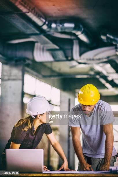 Architekten und Bau Arbeiter, die Pläne zu betrachten