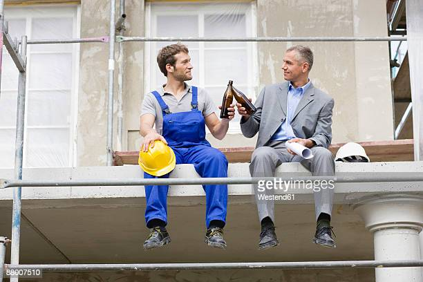 Architect and construction worker on site, drinking beer