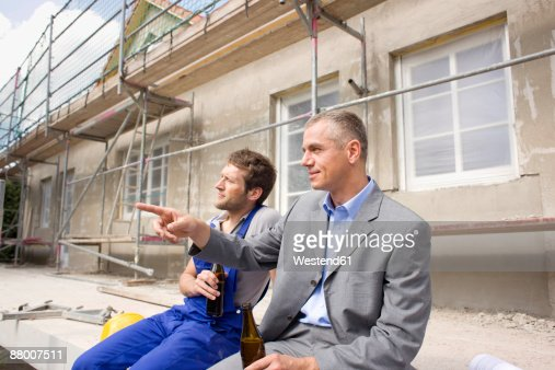 architect and construction worker on site drinking beer stock