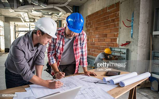Architect And Construction Worker Reviewing Blueprint Together