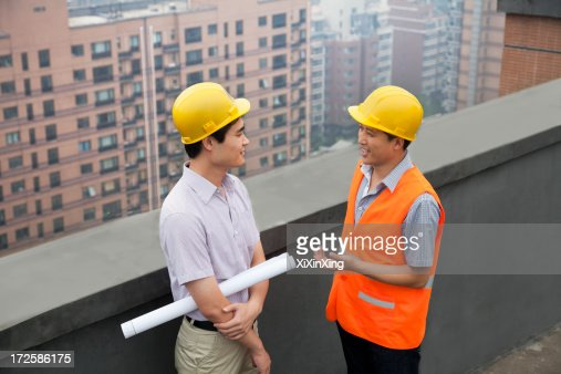 architect and construction worker talking on rooftop stock photo