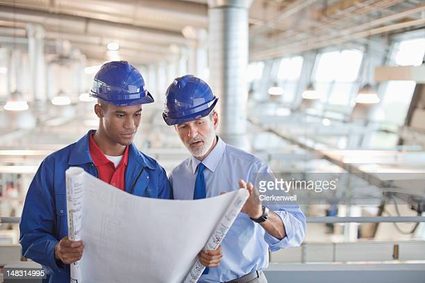 Architect and engineer reviewing blueprint in factory