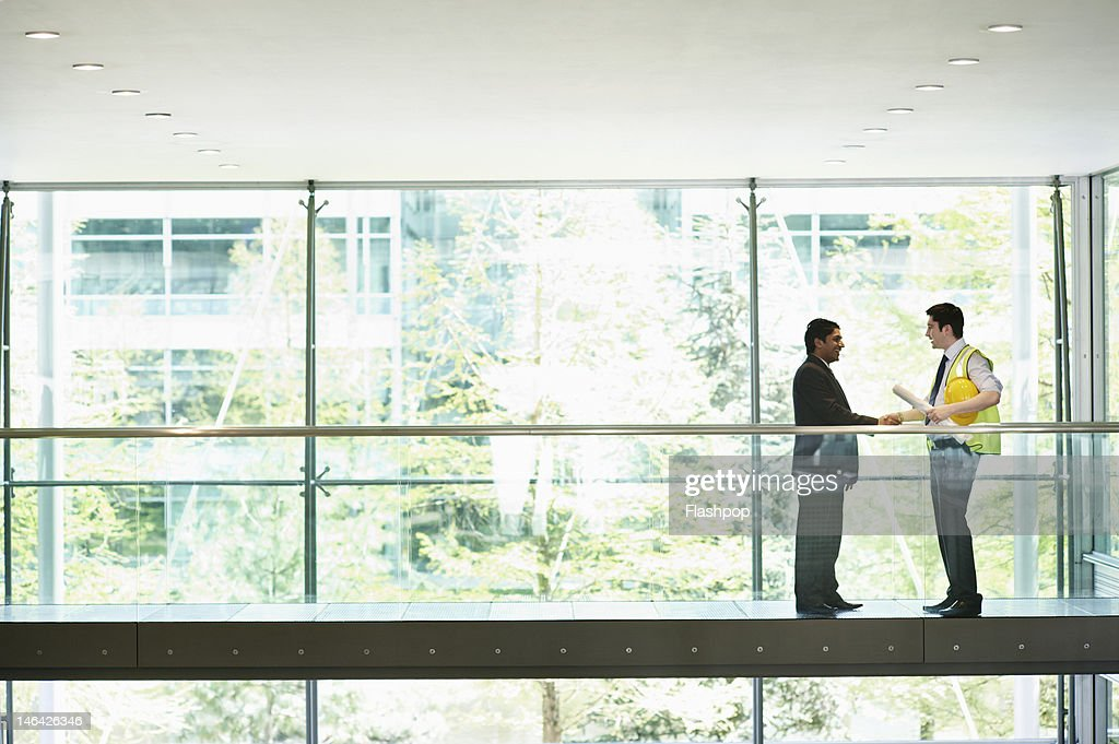 Architect and engineer shaking hands : Stock Photo
