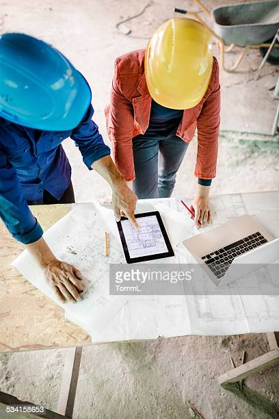 Architect And Foreman With Laptop On Site