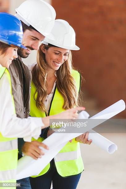 Architect and workers lookig at building plans.
