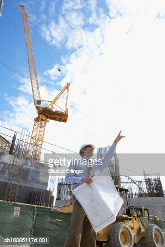 Architect at construction site, holding blueprint and pointing upwards, low angle view : Stock Photo