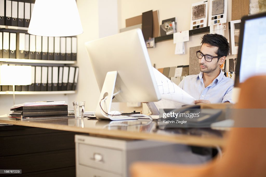 architect at desk examining plans : Stock Photo