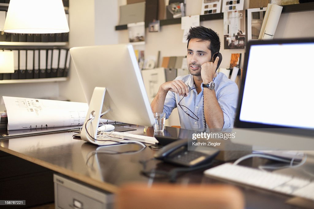 architect at desk talking on the phone : Stock Photo