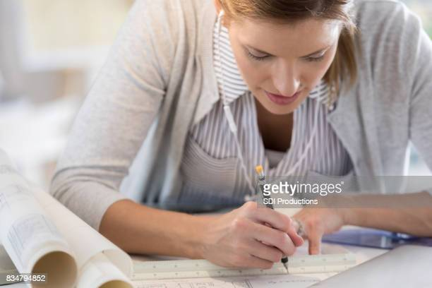 Architect concentrates while drawing blueprint