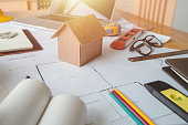 Business objects of engineer or architect on desk with engineer tools and architect analyzer working with blueprints and model house for startup new construction project in office.Engineering tools.
