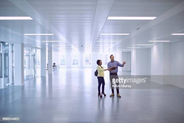 Architect discussing project with colleague in empty office