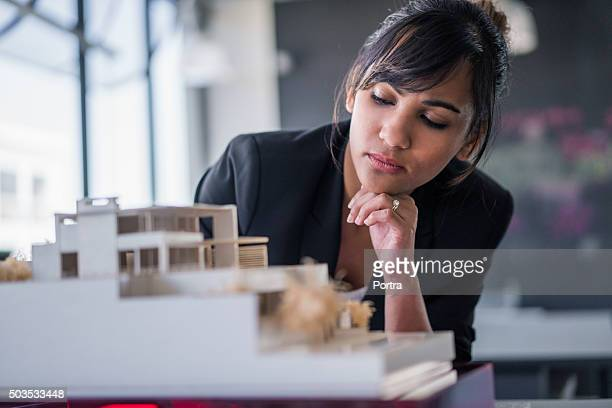 Architect examining artificial model at workplace