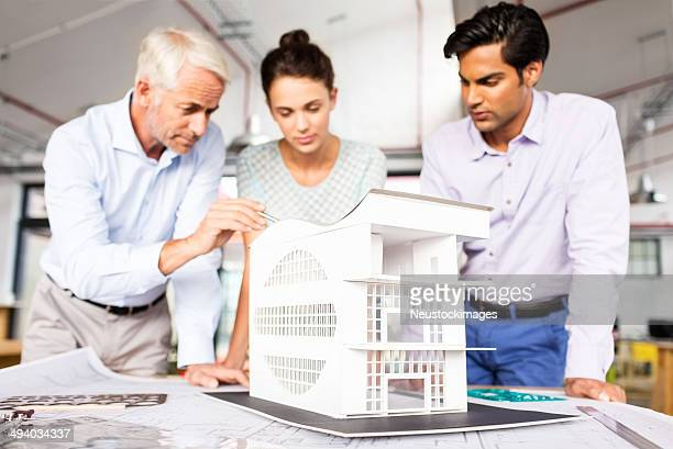 Architect Explaining House Model To Colleagues At Office Desk