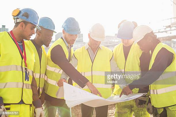 Architect explaining plan on blueprint to construction workers at site