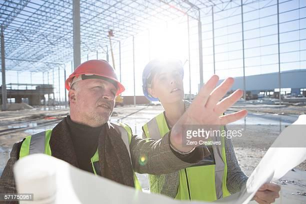 Architect explaining to builder on construction site