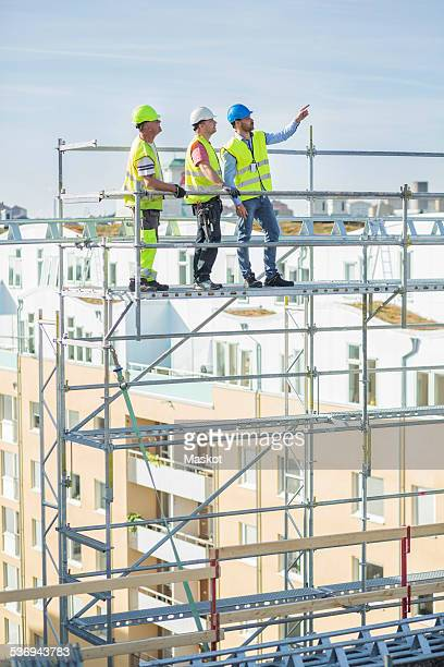 Architect explaining to colleagues while standing on scaffolding at site
