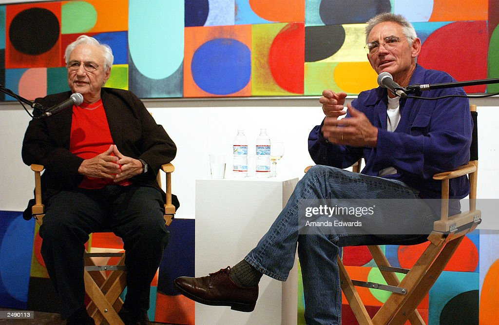Architect Frank Gehry answers questions with artist Chuck Arnoldi (R) at the Santa Monica Museum of Art's Party with Frank Gehry at Chuck Arnoldi's art studio on September 12, 2003 in Venice, California.