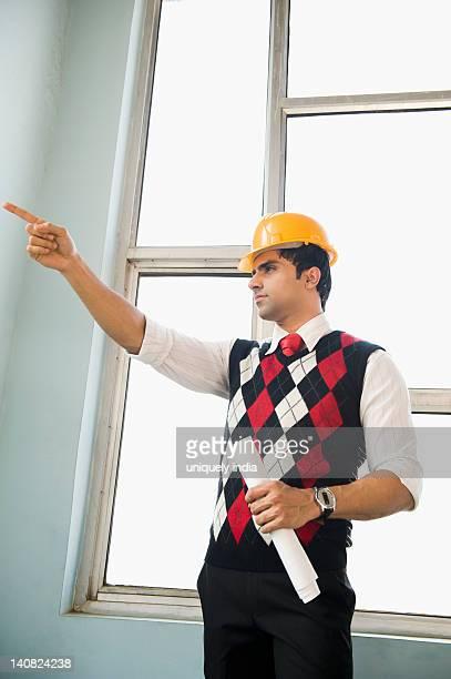 Architect holding a blueprint and pointing upward