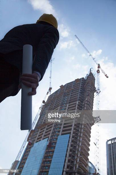 Architect holding blue print and looking up, low angle view