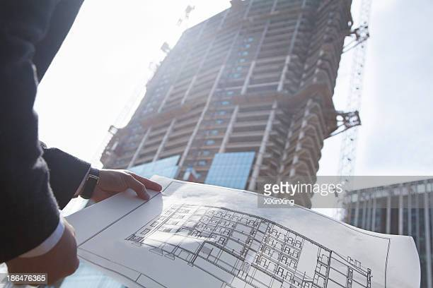 Architect holding blueprint of building at a construction site, midsection