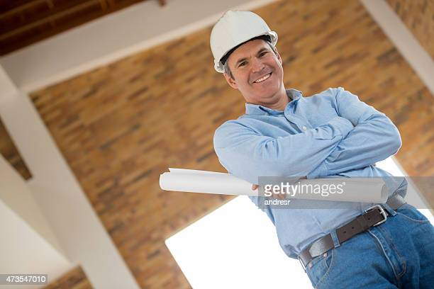 Architect holding blueprints at a construction site
