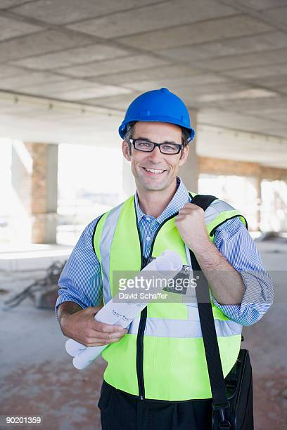 Architect in hard-hat and safety vest on construction site