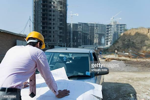 Architect looking at a blueprint at a construction site, Gurgaon, Haryana, India