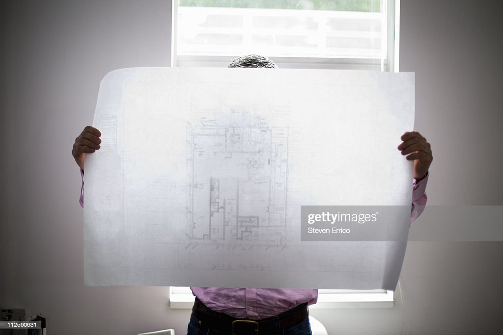 Architect looking at blueprints, silhouetted : Stock Photo