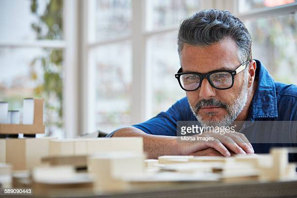 Architect looking at building model in office