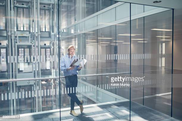 Architect looking at paperwork in office hallway