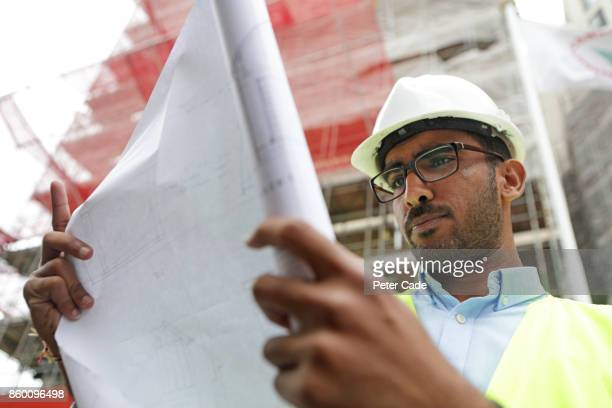 Architect looking at plans on building site