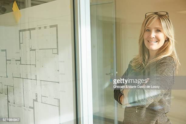 Architect looking at plans taped to glass wall