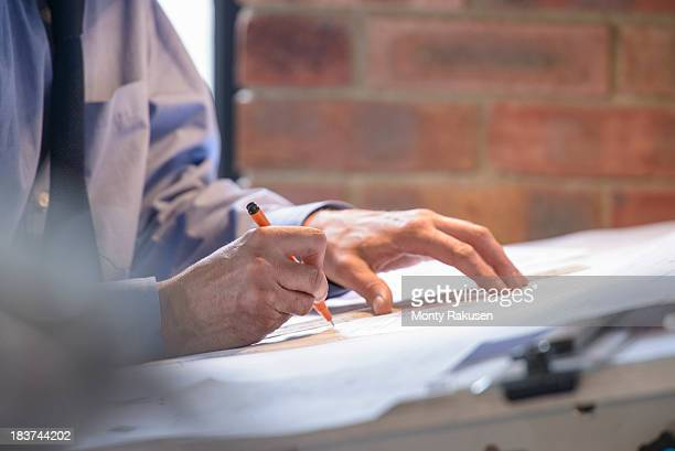 Architect making plans at drawing board, close up