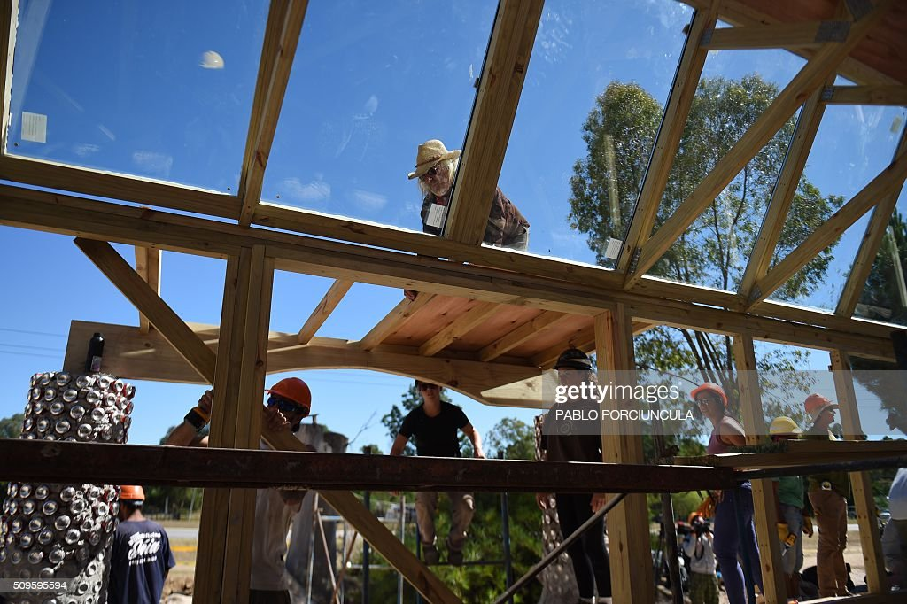 US architect Michael Reynolds (C up) and trainees work during the construction of an auto-sustainable elementary school in Jaureguiberry -80 km east of Montevideo, Uruguay- on February 11, 2016. Reynolds, founder of Earthship Academy, gives training to 100 students from 30 countries (most of them architects) in Earthship design principles, construction methods and philosophy, to build the first school of this kind in the world. AFP PHOTO / PABLO PORCIUNCULA / AFP / PABLO PORCIUNCULA