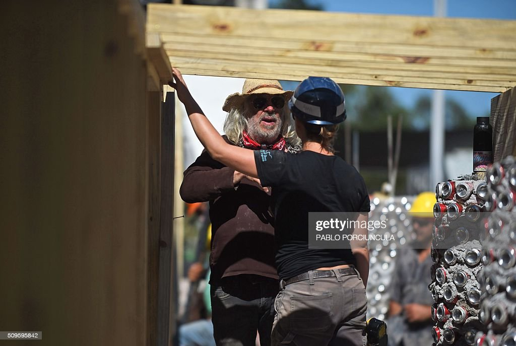 US architect Michael Reynolds (L) speaks with a trainee during the construction of an auto-sustainable elementary school in Jaureguiberry -80 km east of Montevideo, Uruguay- on February 11, 2016. Reynolds, founder of Earthship Academy, gives training to 100 students from 30 countries (most of them architects) in Earthship design principles, construction methods and philosophy, to build the first school of this kind in the world. AFP PHOTO / PABLO PORCIUNCULA / AFP / PABLO PORCIUNCULA