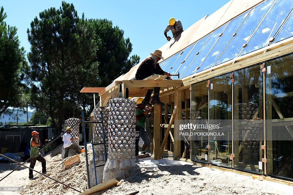 US architect Michael Reynolds (C) works during the construction of an auto-sustainable elementary school in Jaureguiberry -80 km east of Montevideo, Uruguay- on February 11, 2016. Reynolds, founder of Earthship Academy, gives training to 100 students from 30 countries (most of them architects) in Earthship design principles, construction methods and philosophy, to build the first school of this kind in the world. AFP PHOTO / PABLO PORCIUNCULA / AFP / PABLO PORCIUNCULA