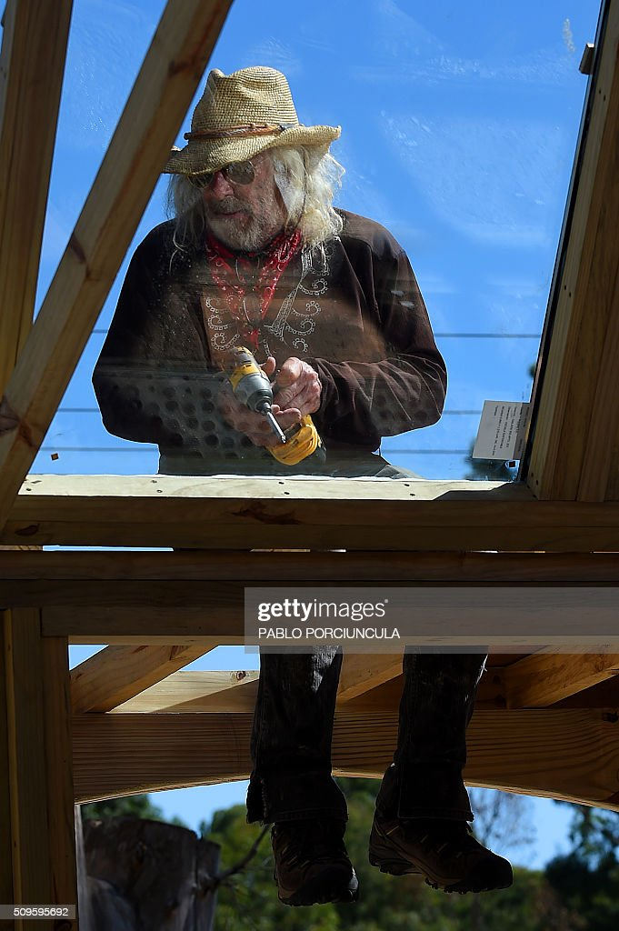 US architect Michael Reynolds works during the construction of an auto-sustainable elementary school in Jaureguiberry -80 km east of Montevideo, Uruguay- on February 11, 2016. Reynolds, founder of Earthship Academy, gives training to 100 students from 30 countries (most of them architects) in Earthship design principles, construction methods and philosophy, to build the first school of this kind in the world. AFP PHOTO / PABLO PORCIUNCULA / AFP / PABLO PORCIUNCULA
