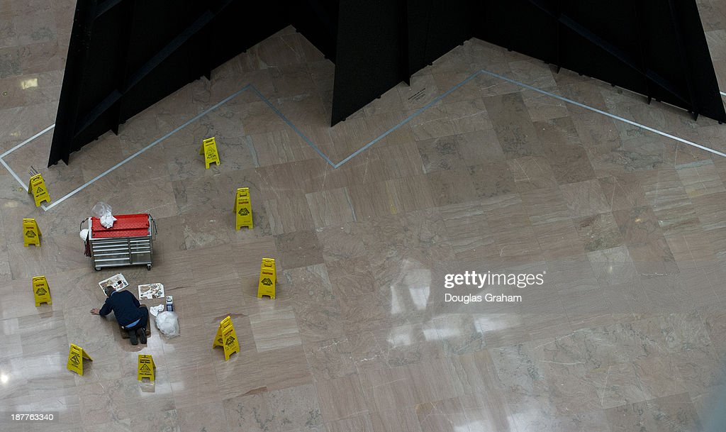 A Architect of the Capitol worker makes repairs to sections of the floor in the Hart Senate Office Building atrium in Washington, D.C. on November 12, 2013.