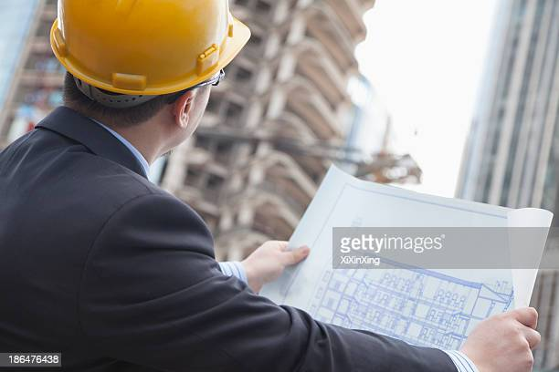 Architect on site looking at blueprints