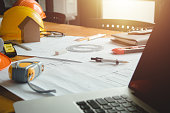 Business objects of architect on desk with engineer tools and architect analyzer working with blueprints and model house,Team meeting concept.Project ideas concept.Vintage effect,selective focus.