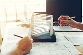 Architect or engineer meeting in office on blueprint And model building. Architects workplace