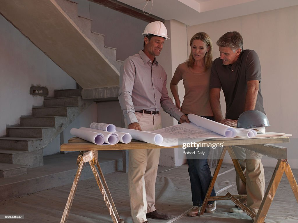 Architect posing with blueprints : Stock Photo
