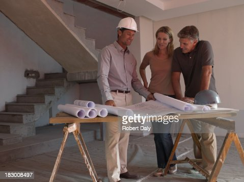 Architect posing with blueprints : Stock Photo