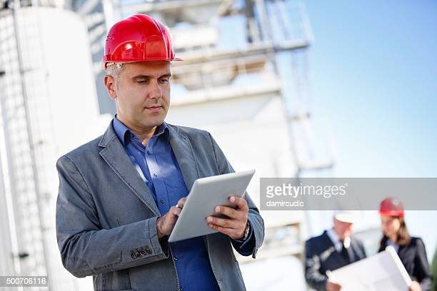 Architect reviewing plans on digital tablet at construction site