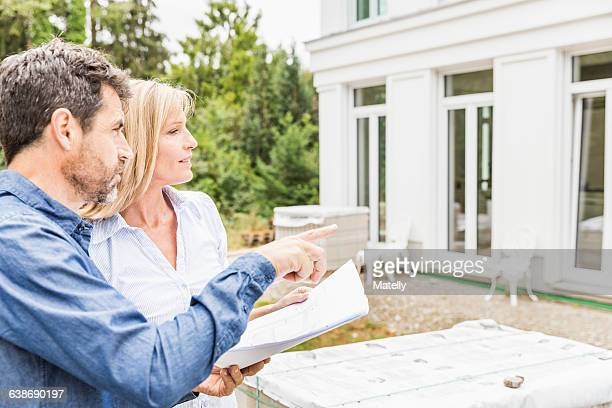 Architect showing homeowner plans for house exterior, looking away pointing