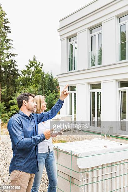 Architect showing homeowner plans for house exterior, looking up pointing
